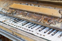 Broken faulty old piano. Piano without keys. Wooden ruined musical instrument.