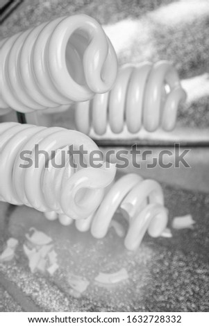 Broken fluorescent spiral tubes, danger of mercury vapor poisoning. Fallen studio light. Fluorescent light bulbs, energy saving lamps, shards of glass. Crashed constant studio lighting softbox