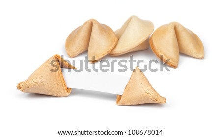 Broken fortune cookie with fortune paper in front of a few other cookies isolated on white.