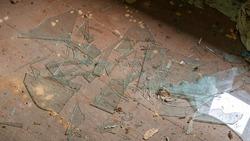 broken fragments of window glass on wooden floor of abandoned building close upper view