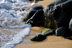 Broken, frothy wave coming toward the rocks on the beach, Waimea Bay, Oahu
