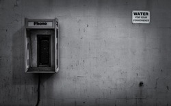 Broken gas station payphone against a painted block with with a water spigot and sign