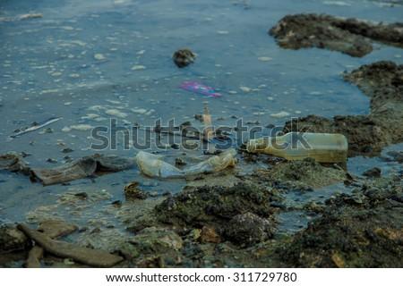 broken glass bottle on sea beach is water pollution