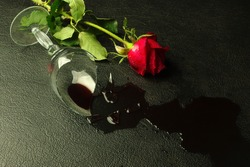 Broken glass of wine and red rose