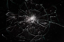 Broken glass on black background with lots of glass splinters and cracks