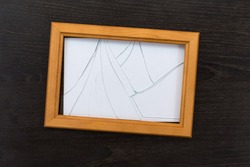 Broken glass photo frame on a wooden table