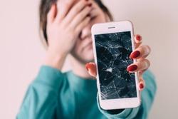 Broken glass screen smartphone in hand of upset girl, white background.