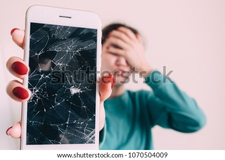 Broken glass screen smartphone in hand of upset girl, white background.