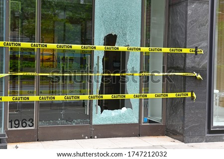 Broken glass window on retail store front from criminals looting and rioting in Manhattan New York during racial protests