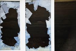 Broken glass window outside. Close up photo of a hole in a broken window