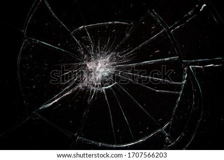Broken glass with lots of cracks, studio shot with black background
