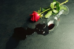 Broken glass with spilled wine and a red rose on a dark background