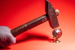broken globe. A model of the globe is broken by a hammer.