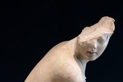 Broken head of marble statue of young man