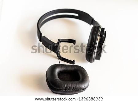 broken headphone, detachable headphones at work. concept of bad quality  listening earphones with copyspace  - image
