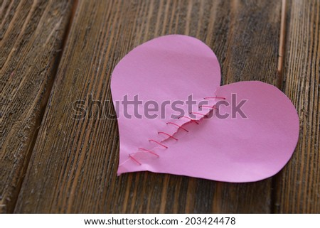 Broken heart and thread on wooden background #203424478