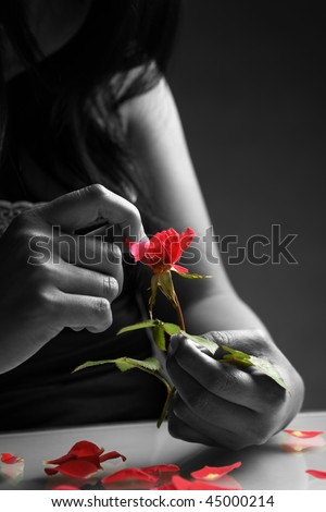 Broken heart girl picking rose petals in black and white except the rose