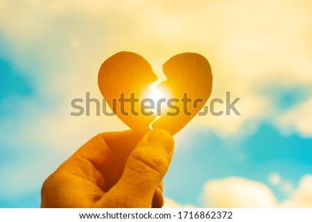 Broken heart in a man's hand on a sunset background. Parting, stop loving, break your heart. Divorce
