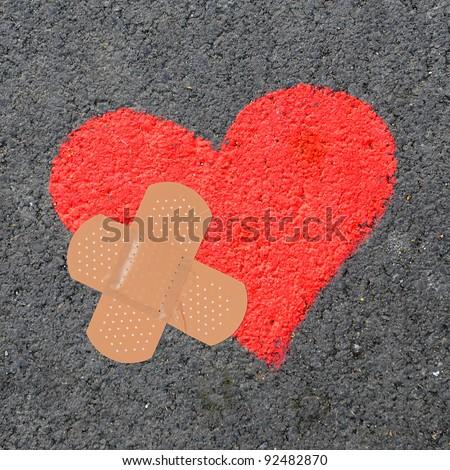 Broken heart with bandage on asphalt