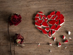 Broken heart with broken red glass and couple red rose dry on wood background for break my heart love, pain, sad. Accompanying sadness article. heart couple or heart poster. valentine concept.