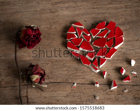 Broken heart with broken red glass and red rose dry on wood background for break my heart background. Accompanying sadness article. heart couple or heart poster.