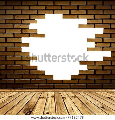 broken hole in the brick wall of room with wooden floor