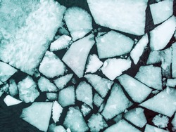 Broken ice background as a concept of blue frigid cold temperatures as in the arctic polar climate with chunks of below zero frozen water representing cool refrigerated environment.