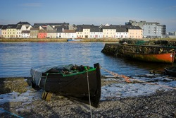 broken ice on the bank of Corrib river and boats in Claddah, Galway