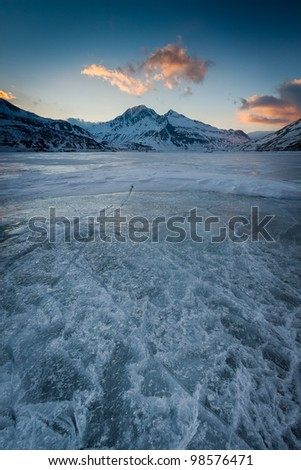 Broken iced lake at sunset. Moncenisio lake, Piedmont, Italy