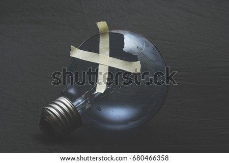 Broken Idea, a broken lightbulb is crudely taped together showing how a cheap solution renders useless results #680466358