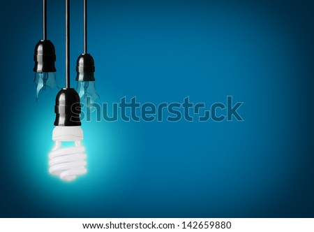 broken light bulbs and energy saver bulb on blue background