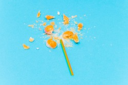 broken Lollipop on blue background with multicolored plastic handle top view