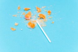 broken Lollipop on blue background with white plastic handle