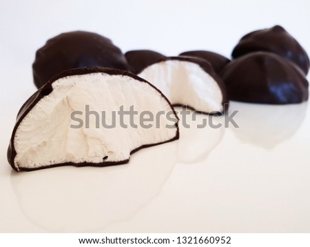 Broken marshmallow in chocolate with whole marshmallows on white marshmallows on white surface. Studio. #1321660952