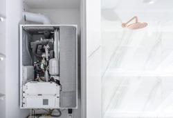 Broken Modern Water Gas Heater Next to Shower Cabin Inside Elegant Clean Bathroom Interior.