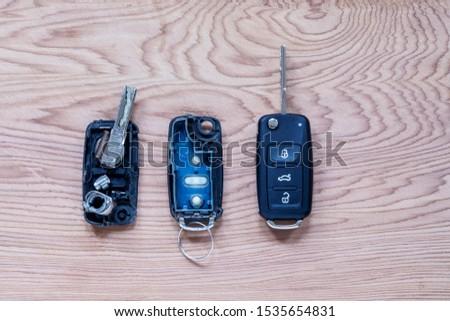 Broken or damaged remote key fob and new vehicle key on wooden background. Broken or damaged remote key fob of any vehicle car locksmith service.- Image