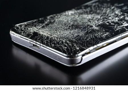 Broken phone on black background, phone repair advertisement, broken screen in smartphone