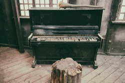 Broken piano in an old dirty building. Dusty wooden room with a forgotten musical instrument