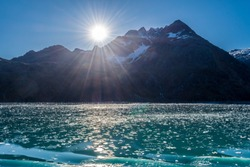 Broken pieces of ice from glaciers floating in the lake. Snow capped mountains in background on a sunny day. Cruise Ship tour through Glacier Bay, Alaska.
