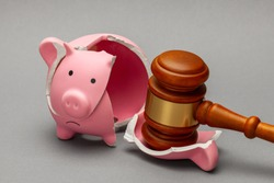 Broken piggy bank and judge gavel