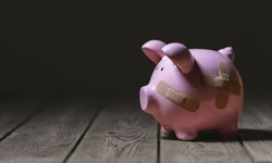 Broken piggy bank with band aid bandage or plaster finance background concept for economic recession or bankruptcy