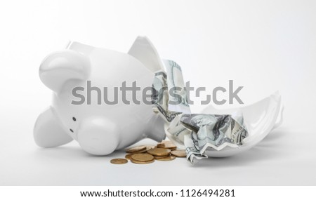 Broken piggy bank with coins and banknotes on white background #1126494281