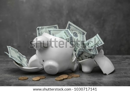 Broken piggy bank with money on table