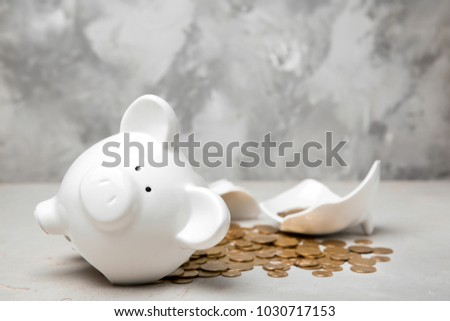Broken piggy bank with money on table #1030717153