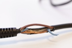 Broken power cord for home electrical appliances, electric tools. Damaged cable insulation. Close-up, soft focus.