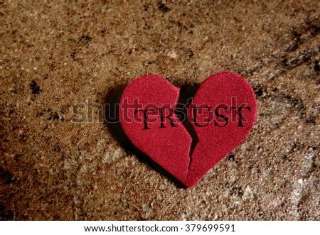 Broken red Trust heart, on textured background