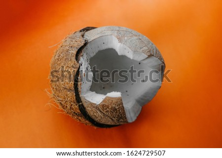 Broken ripe coconut with juicy pulp on a bright orange plain background, volumetric image of tropical fruit
