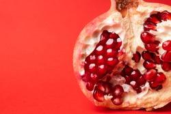 Broken ripe pomegranate fruit on a red background. juicy pomegranate berries. background.