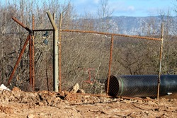 Broken rusted old wire fence with strong metal pipe frame and barb wire on top preventing access to local construction site surrounded with large diameter pipe and dense trees without leaves