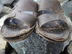 Broken sandals on a rock